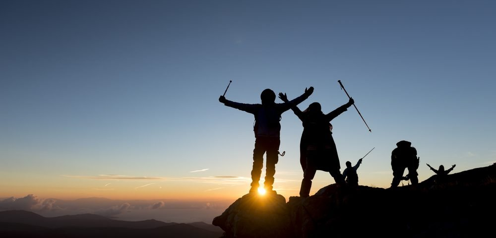 Silhouette of several hikers on the top of a mountain raising their arms in victory as the sun rises behind them.