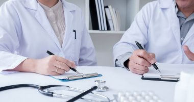 guidelines | ANCA Vasculitis News | Treatments | Two people in lab coats write on clipboards in office setting